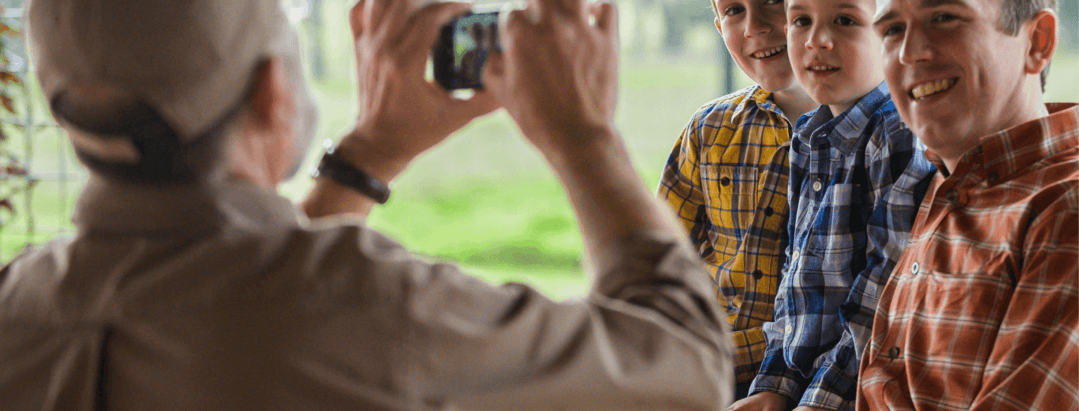 man taking image of different generations of family